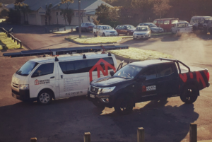 Newton Roofing company vehicles next to one another on the job in Wellington.